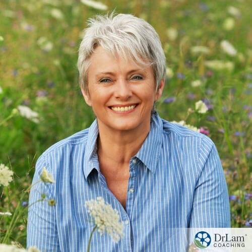 woman smiling in a field of flowers with delay menopause