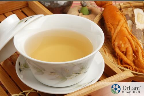 cup of ginseng drinking tea with a ginseng root on table