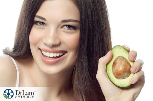 Young healthy girl holding an Avocado health benefits in her hand
