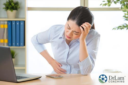 Young woman holding stomach in pain from Managing IBS