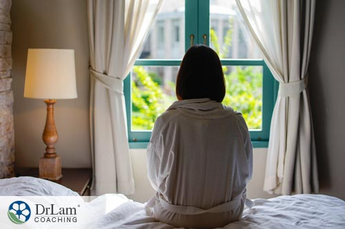 Young woman sitting on the edge of bed looking out into window thinking about pursuit of goals
