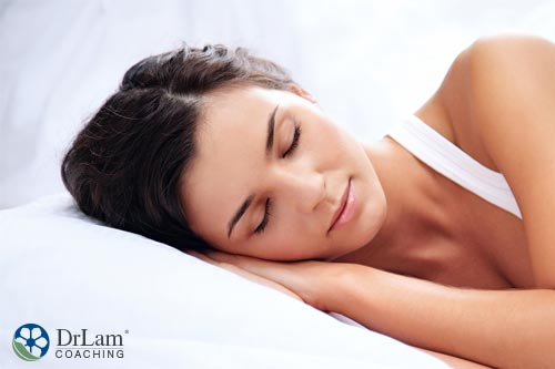 A healthy young woman pleasantly sleeping on her side and looking happy with hormones and sleep patterns