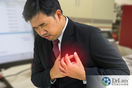 Young man grasping his chest suffering from a heart attack that Natural cholesterol lowering agents could have helped