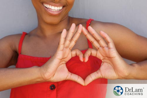Young woman making a shape of heart with her hands will benefit from beta-sitosterol