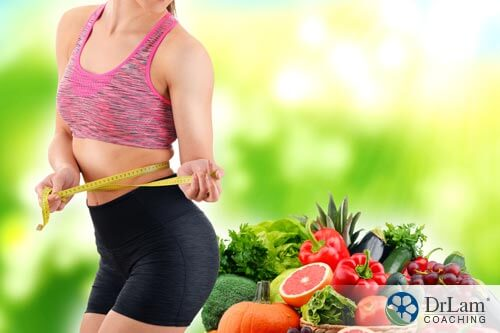 A woman holding a waist measuring tape around her waist and plant based diet next to her