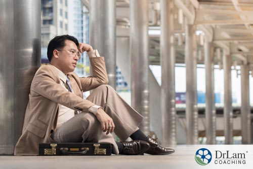 Tired looking man sitting on the ground without the benefits of quercetin