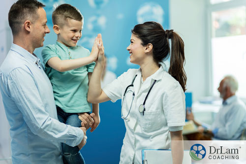 An image of a young boy giving a doctor a high five