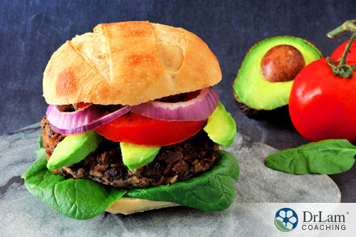An image of a black bean burger on a whole grain bun with avocado, leafy greens, tomatoes and onions