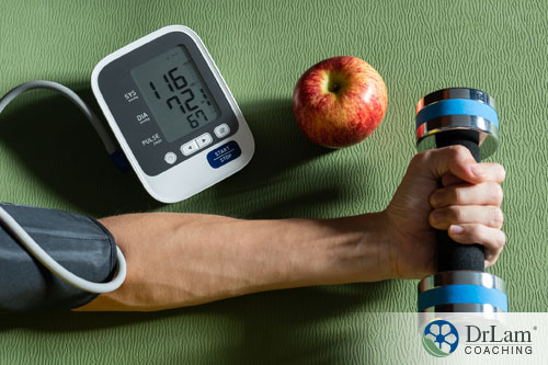 An image of a forarm holding a weight with a blood pressure cuff on the arm taking their blood pressure