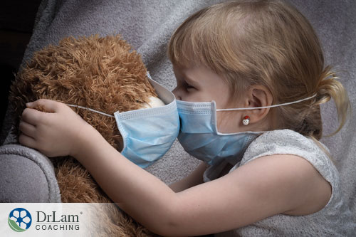 An image of a little girl and her teddy bear wearing protective masks