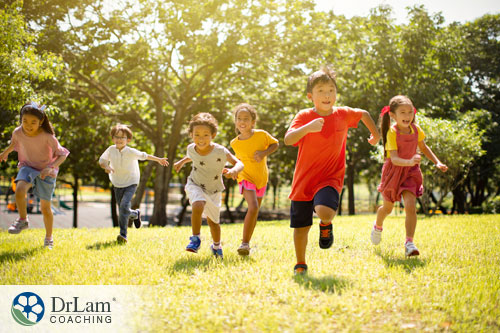 An image of children running and smiling in the sun together