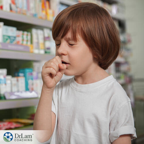 An image of a sick little boy coughing into his hand