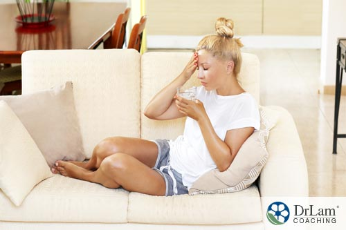 girl sitting on the sofa with a headache. she may consider delay menopause in the future