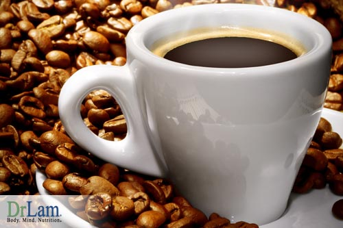 A hot cup of Coffee in the morning surrounded by raw coffee beans.