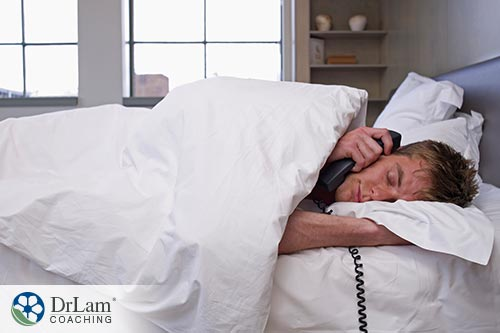 An image of a man laying in bed while holding the phone to his ear