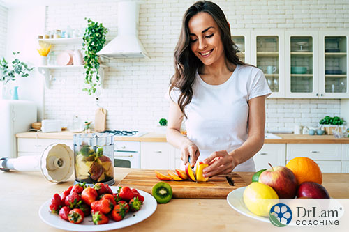 An image of a woman smiling as she slices an apple