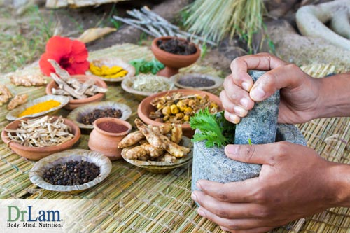 Multiple bowls of herbs and roots including turmeric laid out on a straw mat, and a mortar and pestle being used to grind some ingredients together. Turmeric health benefits are part of longstanding ancient healing traditions.