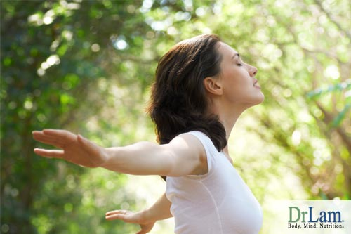 A woman with arms outstretched to the side and eyes closed feeling enjoying the wind and nature, signifying the calming benefits of ashwagandha