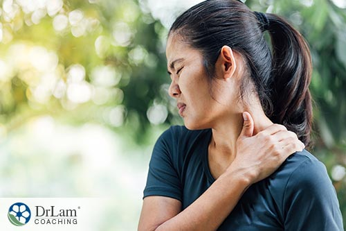 A woman holding her shoulder or lower neck in pain