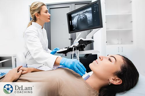 An image of a doctor preforming an ultrasound on a woman's thyroid