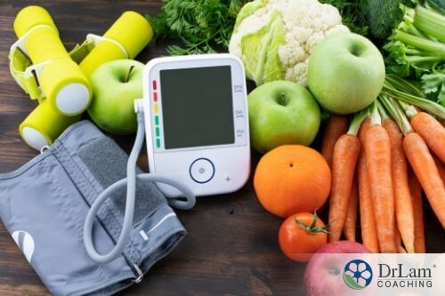 An image of a digital sphygmomanometer with various fruits and vegetables around it