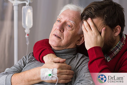 An image of an old man with an IV being held by a young man covering his face in grief