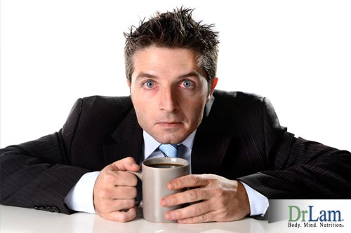 A frazzled looking man clutching a coffee cup, who would benefit from diet changes to soothe hypoglycemia symptoms.