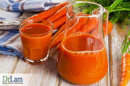 A pitcher and glass of carrot juice and carrots in the background. Eating less while still taking in nutrients can help relax the liver and improve liver health.