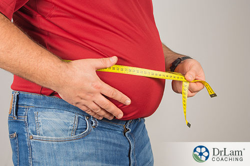 an image of a fat person measuring his belly