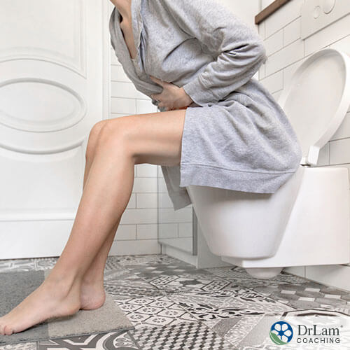 An image of a woman sitting on the toilet holding her abdomen