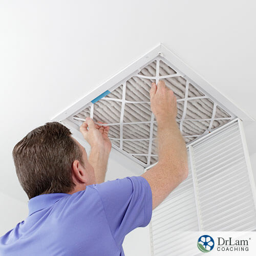 An image of a man changing the air filter