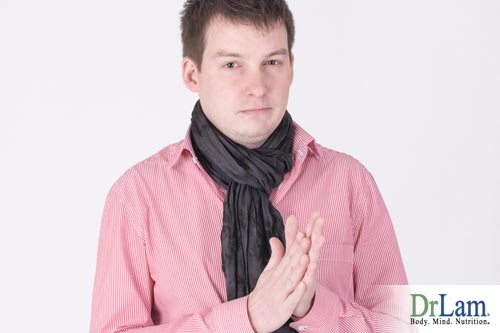 Man in slacks and shirt wearing a scarf and rubbing hands together looking like he may have cold hands and feet.