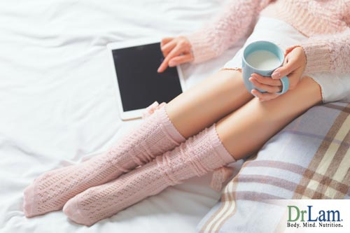 Woman sitting down and relaxing with a mug wearing warm socks to prevent cold hands and feet.
