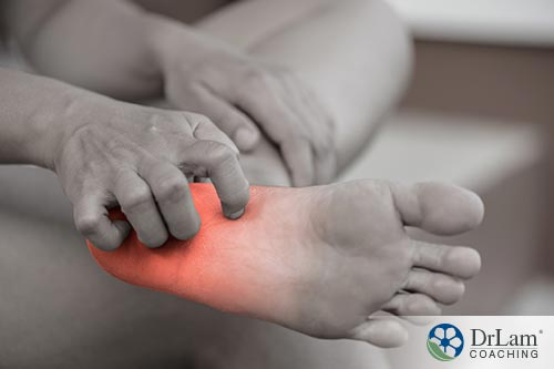 An image of someone itching their inflamed foot