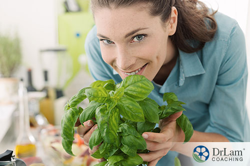 An image of a woman holding a basil plant close to her face smiling