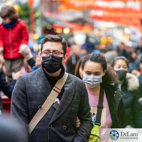 An image of people wearing masks walking in a crowded street