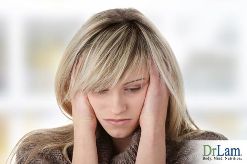 Woman holding the sides of her head and looking depressed. Depression and adrenal fatigue can be deep rooted problems that need a holistic approach.