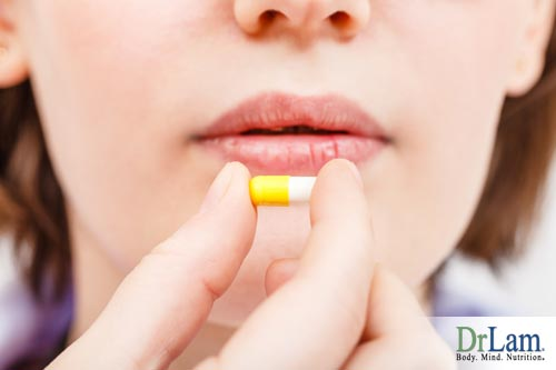 A woman holding a pill capsule of turmeric powder in front of her face near her mouth. Dosed properly, turmeric health benefis can counter many Adrenal Fatigue symptoms.