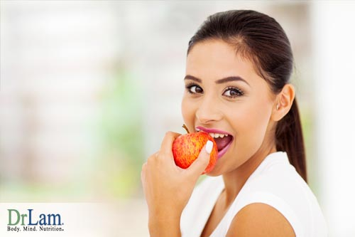 Young woman smiling and biting into an apple. A proper food combining diet will optimize nutrition from food eaten.