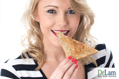 Young woman smiling and eating a slice of toasted bread. Making sure the foods you eat play well together is key to the food combining diet.