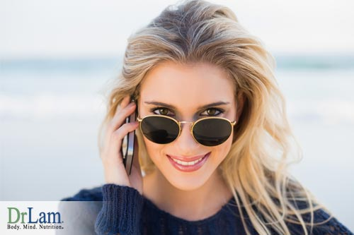 A healthy joyful woman peering over the top of her sunglasses who experiences folic acid benefits