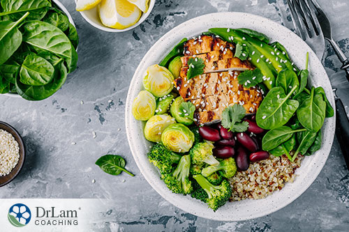 An image of a healthy bowl of quinoa, vegetables and grilled chicken with extra spinach and lemon wedges on the side