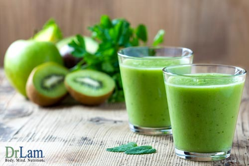Two glasses of green smoothie with ingredients such as kiwi and apple in the background. A simple smoothie with just fruits, vegetables and water is best for the food combining diet.
