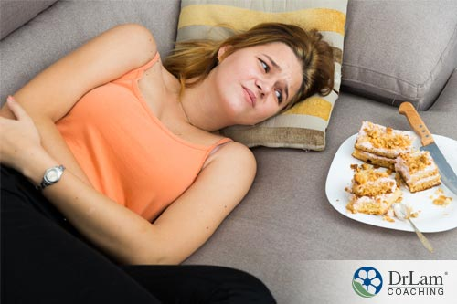 An image of a woman laying on the couch holding her stomach next to a plate of unfinished cake. She is in need of a H2 Blockers to help with her upset stomach