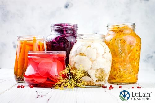 An image of a Variety of fermented vegetables in glass jars, an alternative to taking H2 Blockers