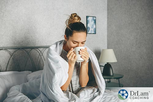 An image of a woman sipping tea in bed