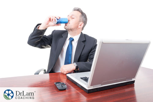 An image of a businessman drinking too many heart threatening energy drinks