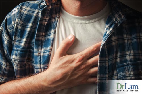 A man holding his chest because of heartburn pain, a possible side effect of taking vitamin C, learn how to safely use antioxidants for cancer