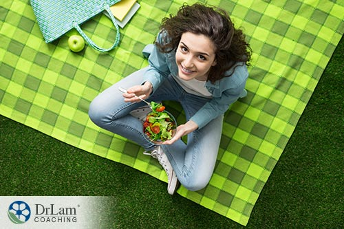 An image of a woman eating a green salad sitting on a green blanket outside