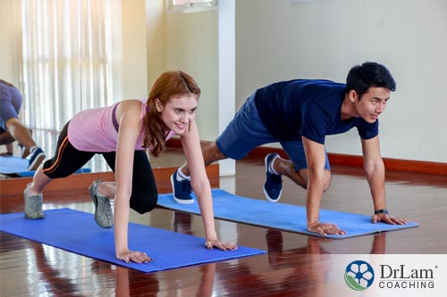 An image of two people, man and woman, doing mountain climbers a high intensity interval training pose
